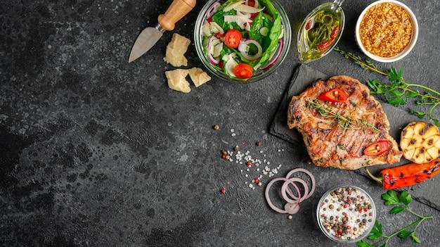暗い石の背景に野菜とスパイスのグリルポークステーキ