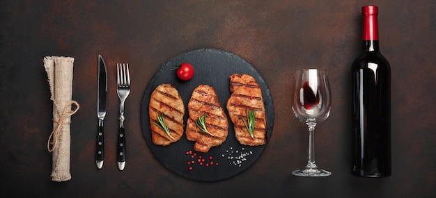 Grilled pork steaks on stone with bottle of wine, wine glass, knife and fork on rusty background. top view with space for your text.