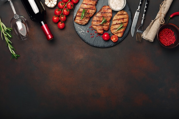 Grilled pork steaks on stone with bottle of wine, wine glass, knife and fork on rusty background