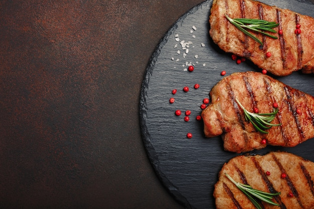 Grilled pork steaks on stone with rosemary and rad pepper on rusty background