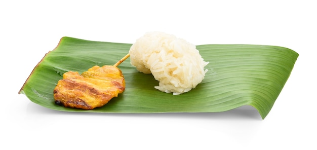 Grilled pork sticky rice on banana leaves and white background thai food
