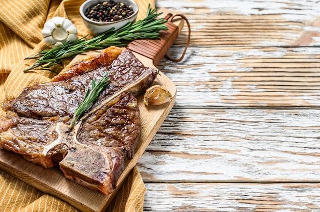 まな板の上でグリルしたポーターハウスステーキ。調理された牛肉。白い木の背景。上面図。スペースをコピーします。