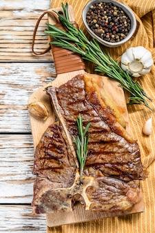 Стейк портерхауз на разделочной доске. приготовленное мясо говядины. белое деревянное пространство. вид сверху
