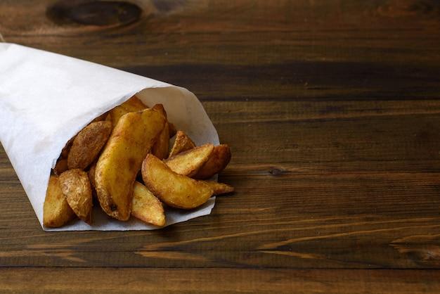 Картофель на гриле в бумажном пакете на темном деревянном фоне