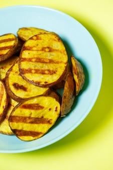 노란색 배경에 파란색 접시에 황금빛 갈색이 될 때까지 구운 감자