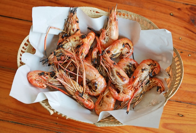 Grilled prawns in basket on wood table. top view.