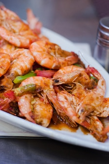 Grilled prawns or shrimps on plate on dark table
