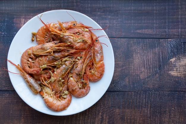 Grilled prawns with garlic on a wooden background