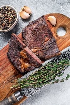 Grilled prime rib eye beef meat steak on a wooden cutting board.