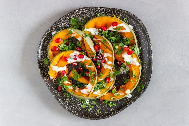 Grilled pumpkin with pomegranate and white sauce. healthy eating.