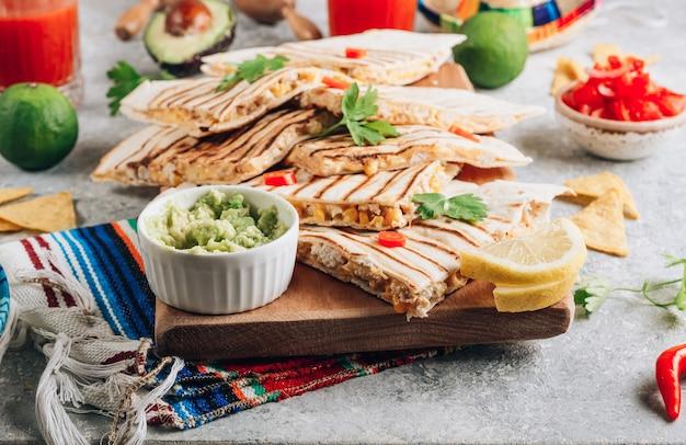 木の板にケサディーヤのグリル、石の背景にサルサとワカモレを添えて。メキシコ料理のコンセプトケサディーヤはチキンとコーンで包みます。セレクティブフォーカス