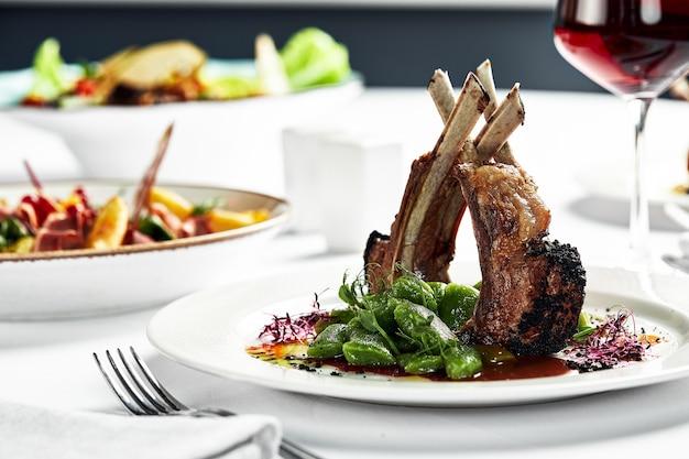 스튜 콩 꼬투리가 있는 하얀 접시에 구운 양고기 랙. 밝은 배경에 와인 한 잔과 함께 구운 양고기.