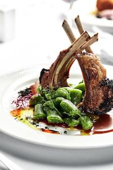若い子羊のグリルラックに豆を添えて、白い皿にザクロのソースを添え、骨に肉をグリルし、宴会テーブルを飾ります。