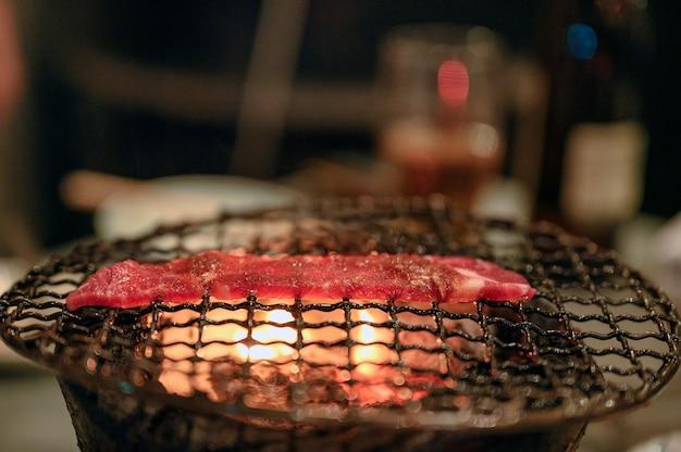 Кусочек сырой говядины на гриле на пылающем угле