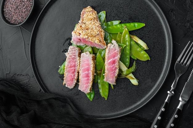 Стейк из редкого красного тунца на гриле с зеленым луком и сахарным горошком, на тарелке, на черном каменном столе, плоская планировка, вид сверху