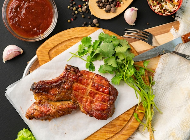 Grilled ribeye beef steak, herb leafs and  spices around, top view with copy space for your texts