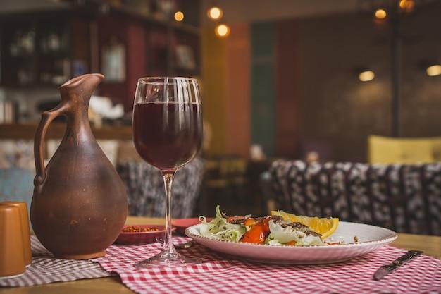 Стейк из говядины рибай с красным вином, зеленью и специями на деревянном столе