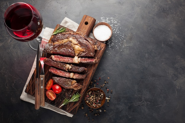 Grilled ribeye beef steak with red wine.