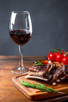 바베큐 소스에 구운 갈비와 테이블에 레드 와인 한 잔