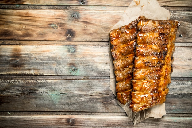 Grilled ribs on old paper on wooden table.