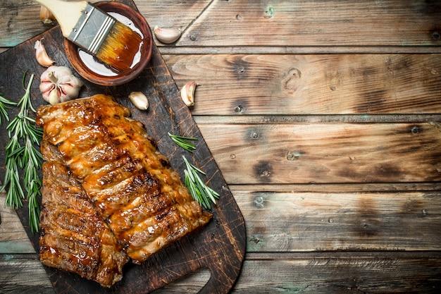 Ребрышки на гриле с розмарином, специями и соусом. на деревянном фоне.