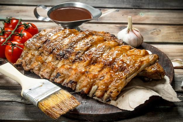 Ребрышки на гриле с томатным соусом и чесноком. на деревянном фоне.