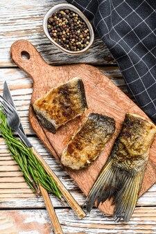 まな板の上の川魚のグリルシルバーコイ。木製の背景。上面図。