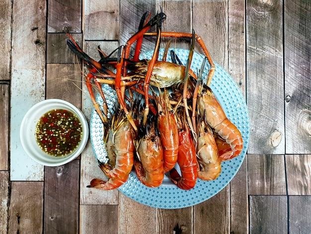 Жареные речные креветки с соусом из морепродуктов на деревянных фоне