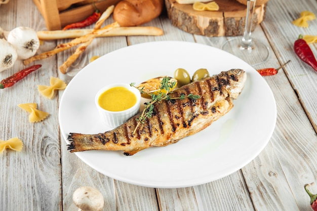 Grilled river trout fish with lemon cream sauce