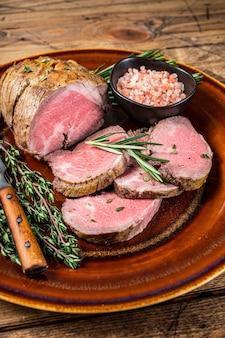 소금으로 소박한 접시에 구운 로스트 비프 등심 고기. 배경. 평면도.