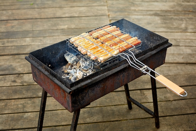 Grilled roast beef and lamb sausages on bbq grid