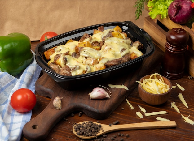 Grilled roasted beef pieces and potato slices in cream melted cheese