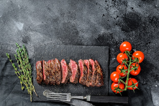 Grilled roasting rare sliced top blade, denver steak. marble meat beef. black surface. top view. copy space