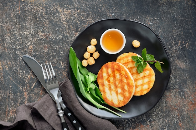 Grilled round slices of greek cheese with honey fresh mint and coriander leaves. flat lay on dark grey table