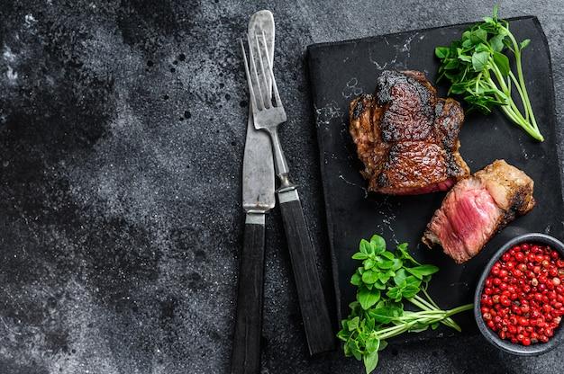 Жареный крупец мраморный стейк из говядины. черный фон