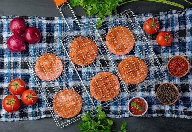 Ломтики салями на гриле. решетка гриля над деревянным столом с овощами.