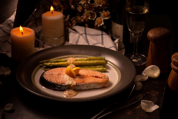 Grilled salmon and asparagus on plate with glass of white wine at dinner time