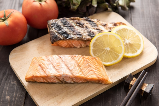 Grilled salmon on cutting board on wooden table.