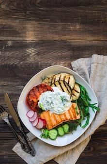 素朴な木製の背景にキノアとザジキソースを添えたサーモン、ナス、トマトのグリル。健康的な夕食。上面図。スペース領域をコピーします。