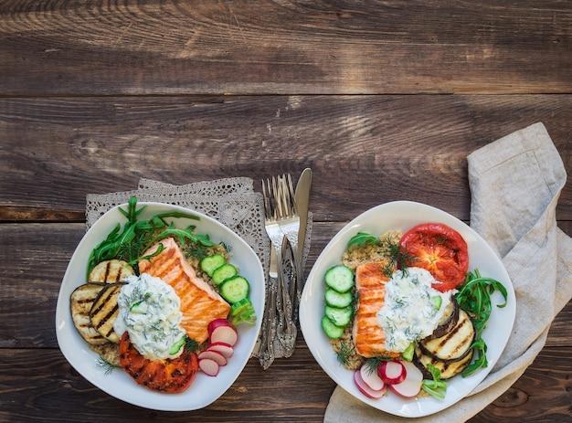 素朴な木製の背景にキノアとザジキソースを添えたサーモン、ナス、トマトのグリル。健康的な夕食。上面図。