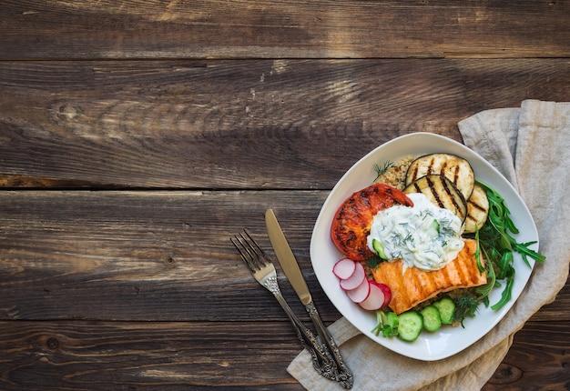 素朴な木製のテーブルにサーモン、ナス、トマトのグリル、キノアとザジキソースを添えて。健康的な夕食。上面図。スペース領域をコピーします。