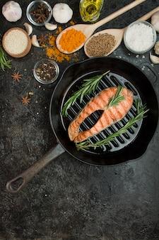 Стейк из лосося на гриле с ароматными травами, специями и овощами в сковороде. морепродукты. концепция приготовления пищи. кулинарный фон. таблица фонового меню. копировать пространство