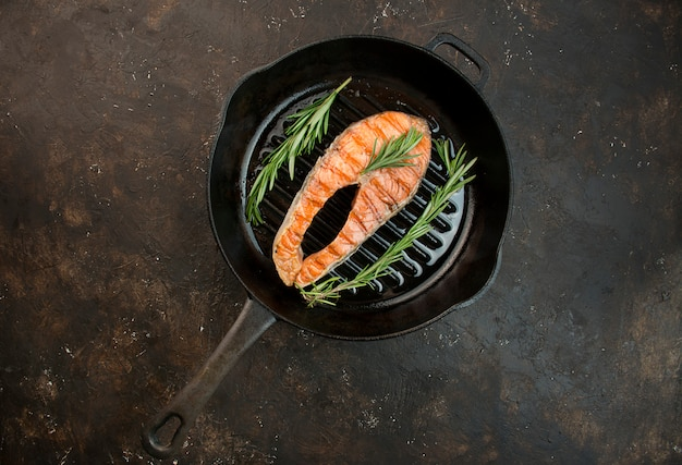 Grilled salmon filet steak with aromatic herbs, spices and vegetables in a grill pan. seafood. cooking concept. culinary background. table background menu. copy space