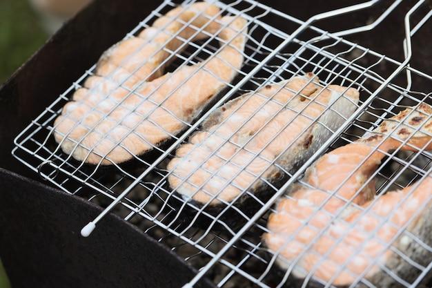 Филе лосося на гриле в металлической решетке для приготовления рыбы на углях