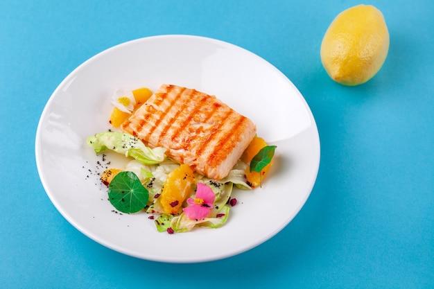 Стейк из филе лосося с гарниром из салата в белой тарелке