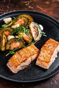 접시에 arugula와 토마토 샐러드를 곁들인 구운 연어 필렛 스테이크. 어두운 배경입니다. 평면도.