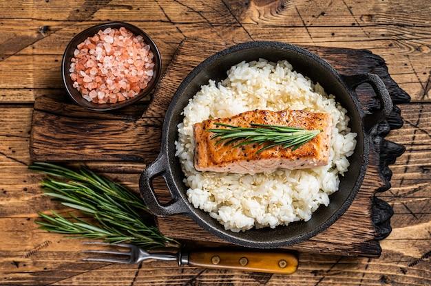 팬에 흰 쌀을 곁들인 구운 연어 등심 스테이크. 나무 배경입니다. 평면도.