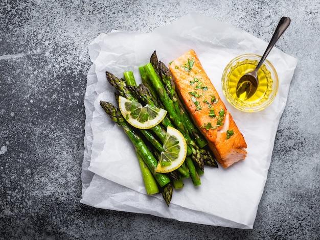 Филе лосося на гриле с зеленой спаржей и приправами, серый бетонный фон. здоровая сбалансированная еда с лососем и спаржей, полезная для диеты и хорошего самочувствия, вид сверху, крупный план