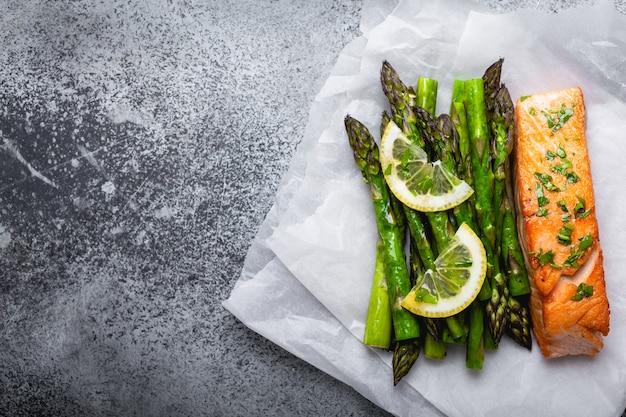 Филе лосося на гриле с зеленой спаржей и приправами, серый бетонный фон, место для текста. здоровый сбалансированный ужин с лососем и спаржей, полезный для диеты и хорошего самочувствия, вид сверху, крупный план