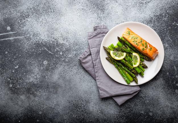 Филе лосося на гриле с зеленой спаржей и приправами на тарелке, сером фоне бетона, копией пространства. здоровый сбалансированный ужин с лососем и спаржей для диеты и хорошего самочувствия, вид сверху, крупный план